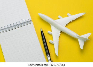 Flat lay of toy airplane with pen and white clean paper notepad on vivid yellow background, travel destination wishlist or planning, holiday and vacation trip planning in flat lay concept.