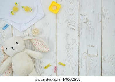 Flat lay toys and Baby Clothing frame on white wooden background. Plush toy hare mockup with copy space for your text