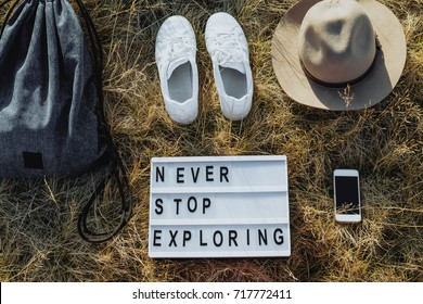 Flat lay travel composition with hat, backpack, white sneakers, phone, board with text Never stop exploring on dry grass, Top view