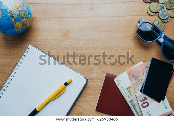 Flat lay travel concept with coins, cards, sunglasses, mobile phone, globe and coffee. Top view