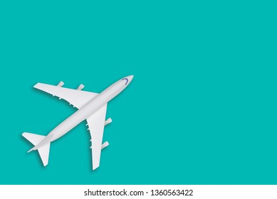 Flat lay travel concept design with plane on tiffany background with copy space. White blank model of a passenger plane.