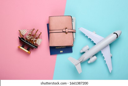 Flat lay travel design. Figurine of a ship, airplane, passport and walet on a blue-pink pastel background. Top view