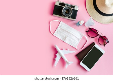 Flat lay of travel item and daily use item for hygiene with surgical mask, alcohol spray and hands sanitizer on pink background, top view and copy space. Travel concept.
