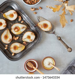 Flat lay with a tray of baked pears with caramelized nuts on gray concrete background with Autumn leaves, sugar and honey