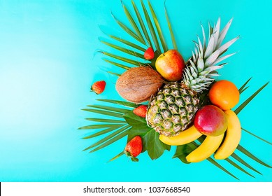 Flat lay of tropical fruits on palm leaves. Pineapple, mango, banans, orange, apple and strawberries. Turquoise background. Copy space. Horizontal.