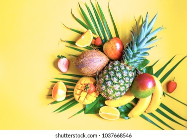 Flat lay of tropical fruits on palm leaves. Pineapple, mango, banans, orange, apple and strawberries. Yellow background. Copy space. Horizontal.