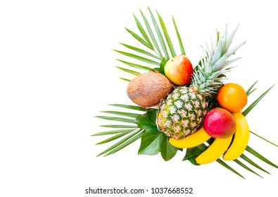 Flat lay of tropical fruits on palm leaves. Pineapple, mango, banans, orange, apple and strawberries. White background. Copy space. Horizontal.