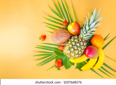 Flat lay of tropical fruits on palm leaves. Pineapple, mango, banans, orange, apple and strawberries. Golden background. Square.