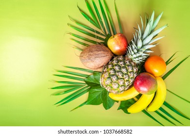 Flat lay of tropical fruits on palm leaves. Pineapple, mango, banans, orange, apple and strawberries. Green background. Copy space. Horizontal.