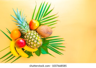 Flat lay of tropical fruits on palm leaves. Pineapple, mango, banans, orange, apple and strawberries. Golden background. Copy space. Horizontal.