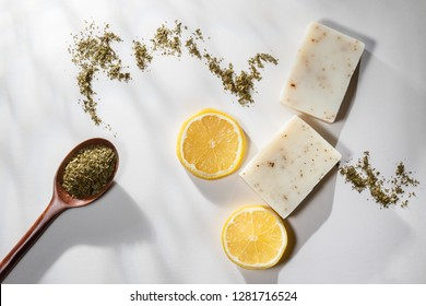 Flat lay of two handmade lemon tea bar soaps with a spoonful of tea leaves and lemon slices