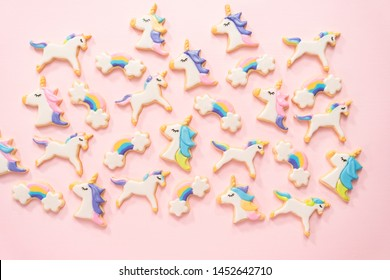 Flat lay. unicorn sugar cookies decorated with royal icing and food glitter on a pink background.