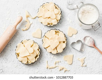 Flat lay Valentine's day baking background. Raw apple tartlets in the baking dish and baking ingredients on light background, top view