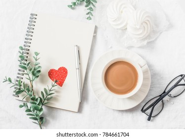 Flat lay Valentine's day breakfast - cocoa with milk, meringues, flowers, notepad, paper hearts decorations, glasses on a light background, top view. Free space for text