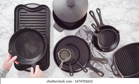 Flat lay. Variety of cast iron kitchenware on a marble countertop.