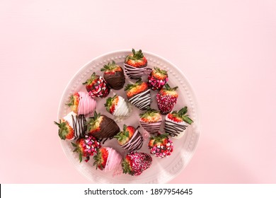 Flat lay. Variety of chocolate dipped strawberries on a pink cake stand.