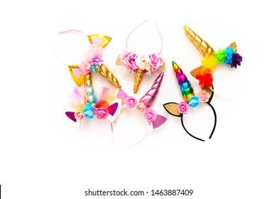Flat lay. Variety of unicorn headbands on a white background.
