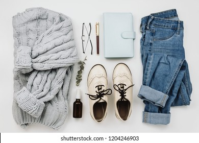 Flat lay of various cozy woman's clothes and accessories on white