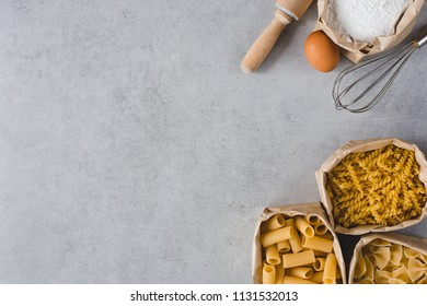Flat lay of various pasta in bag and device for kitchen with space for your text