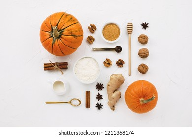 Flat lay with various pumpkins, cinnamon stick, flour, spices, cane sugar and other pumpkin pie ingredients knolled together on white cement background
