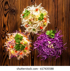 flat lay of vegetarian salads with white, red cabbage, carrot decorated red pepper, cucumber, parsley and garlic on wooden table, concept healthy lifestyle
