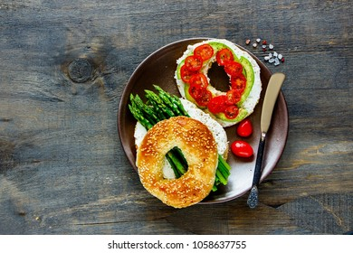 Flat lay of veggie breakfast. Sandwiches with soft cheese, avocado, tomatoes and aspargus on bagels over wooden background. Top view. Healthy, weight loss, clean eating, detox food concept