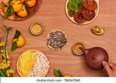 Flat lay Vietnamese new year food and drink on rustic red wooden table top. Text appear in image: Prosperity.