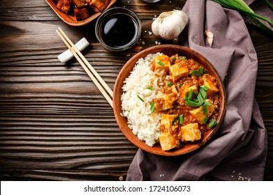 Flat lay view at authentic traditional Chinese food mapo tofu dish with pork chives steamed rice and soy sauce closeup