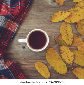Flat lay view of autumn leaves and tartan textured scarf on wooden background with cup of tea - Autumn concept