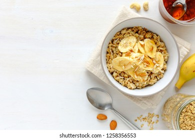 Flat lay view of breakfast set with banana oatmeal in bowl against white table with copy space