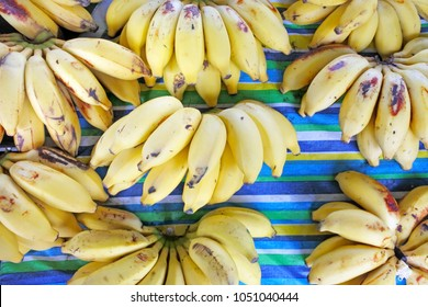 Flat lay view of bunch of bananas for sale in Rarotonga market, Cook Islands. The high content of potassium in bananas makes it a super fruit. Food background and texture. Copy space