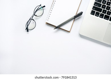 Flat lay view of laptop, glasses, notepad & pen with copy space on white desk table. Lifestyle concept.
