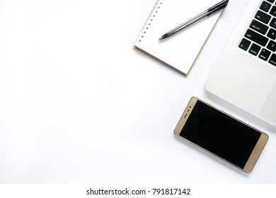 Flat lay view of laptop, smartphone, notepad & pen with copy space on white desk table
