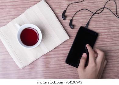 Flat lay view of a man's hand having morning tea or hi-tea.