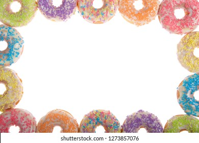 Flat lay view of many Frosted donuts with candy sprinkles arranged in a border frame isolated on white