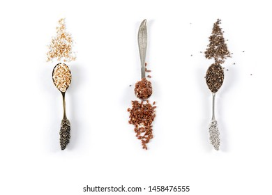 Flat lay view of metal  spoons filled with sesame seeds, chia seeds and ground flax seeds. Heart healthy super food concept. Top view. Isolated on white background.