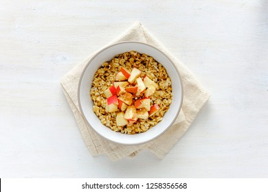 Flat lay view of oatmeal with apple in bowl against white table