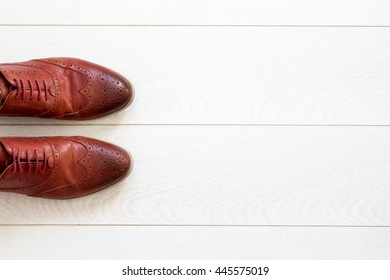 Flat lay view on classic brown men`s shoes on white wooden background. Top view.