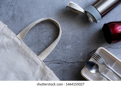 Flat lay or to view of reusable packaging consists of a beige cotton shopping bag, aluminum water tumbler, red coffee mug, and a lunch box on the grey naked concrete with the crack background.