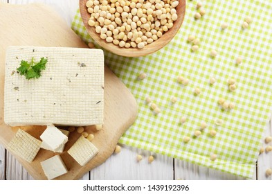 Flat lay view at Soy Bean curd tofu on cutting board with bowl of beans aside. Non-dairy alternative substitute for cheese