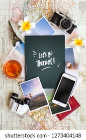 """Flat lay view of summer vacations planning related objects on world map background. Text appear in image"""" Let's Travel!""""."""
