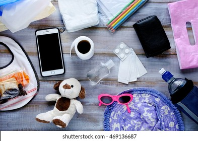Flat lay view of toddler diaper bag essentials on a wooden table. Family and children lifestyle concept.