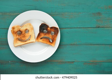 Flat lay view of two slices of toasted bread in a white plate. One is burned and one is well done. Relationship lifestyle concept. copy space
