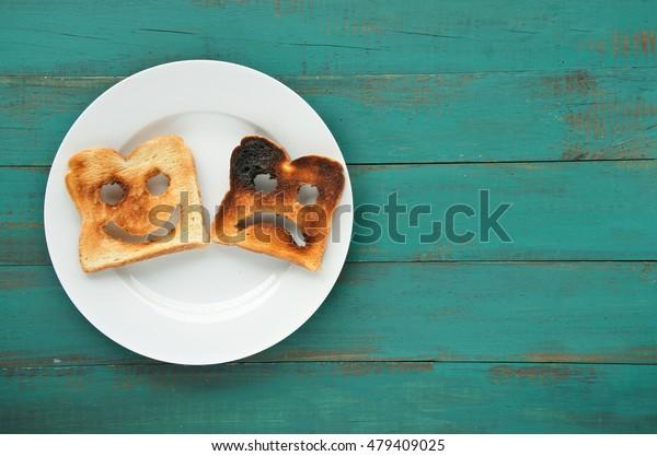 Плоский вид из двух ломтиков поджаренного хлеба в белой тарелке. Один сожжен, а другой хорошо сделано. Концепция образа жизни отношения. Копировать пространство
