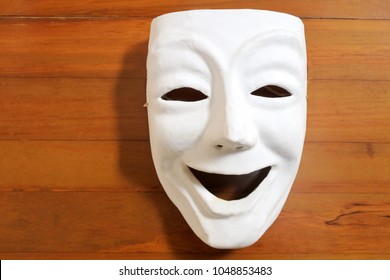 Flat lay view of a white happy human face expression mask with on a wooden table. Happiness concept. Copy space