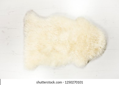 Flat lay view of white warm and cozy whole real decorative sheepskin rug on white wooden board floor.  Room for text. Studio set.