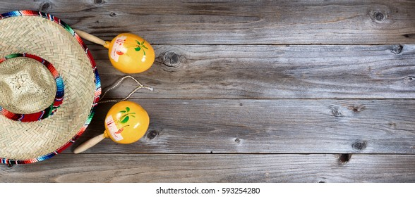 Flat lay view of yellow maracas and large sombrero on rustic red wooden boards for Cinco de Mayo concept. Plenty of copy space.