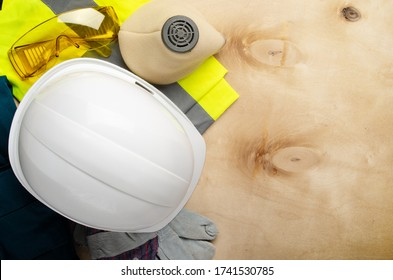 Flat lay view at yellow plastic hard hat, glasses, respirator, reflective vest and protective gloves laying on plywood. Safe labor concept