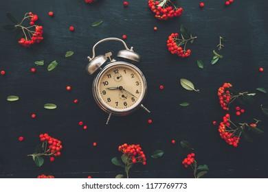 Flat lay vintage alarm clock on dark black background, top view minimal composition with retro floral arrangement