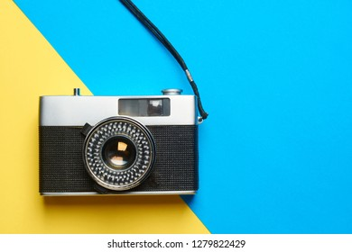 Flat lay vintage camera on colorful background with copy space.